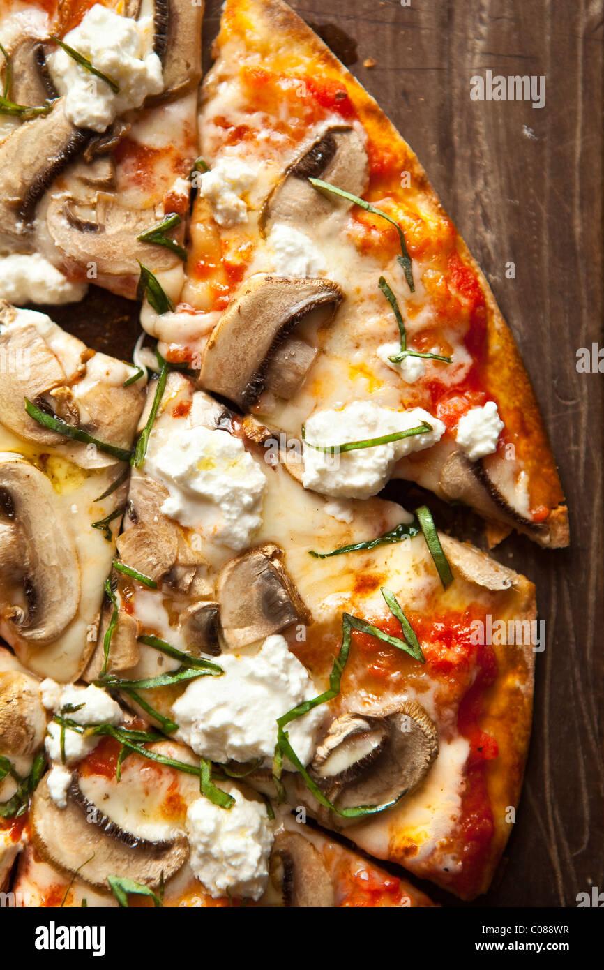 Dünne und knusprige Kruste Pizza mit Mozzarella, Champignons, Ziegenkäse und Basilikum von Gianni Scappin, Stockbild