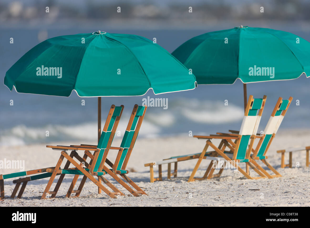 Freie Liegestühle und Sonnenschirme an einem sonnigen Tag am Strand. Stockbild