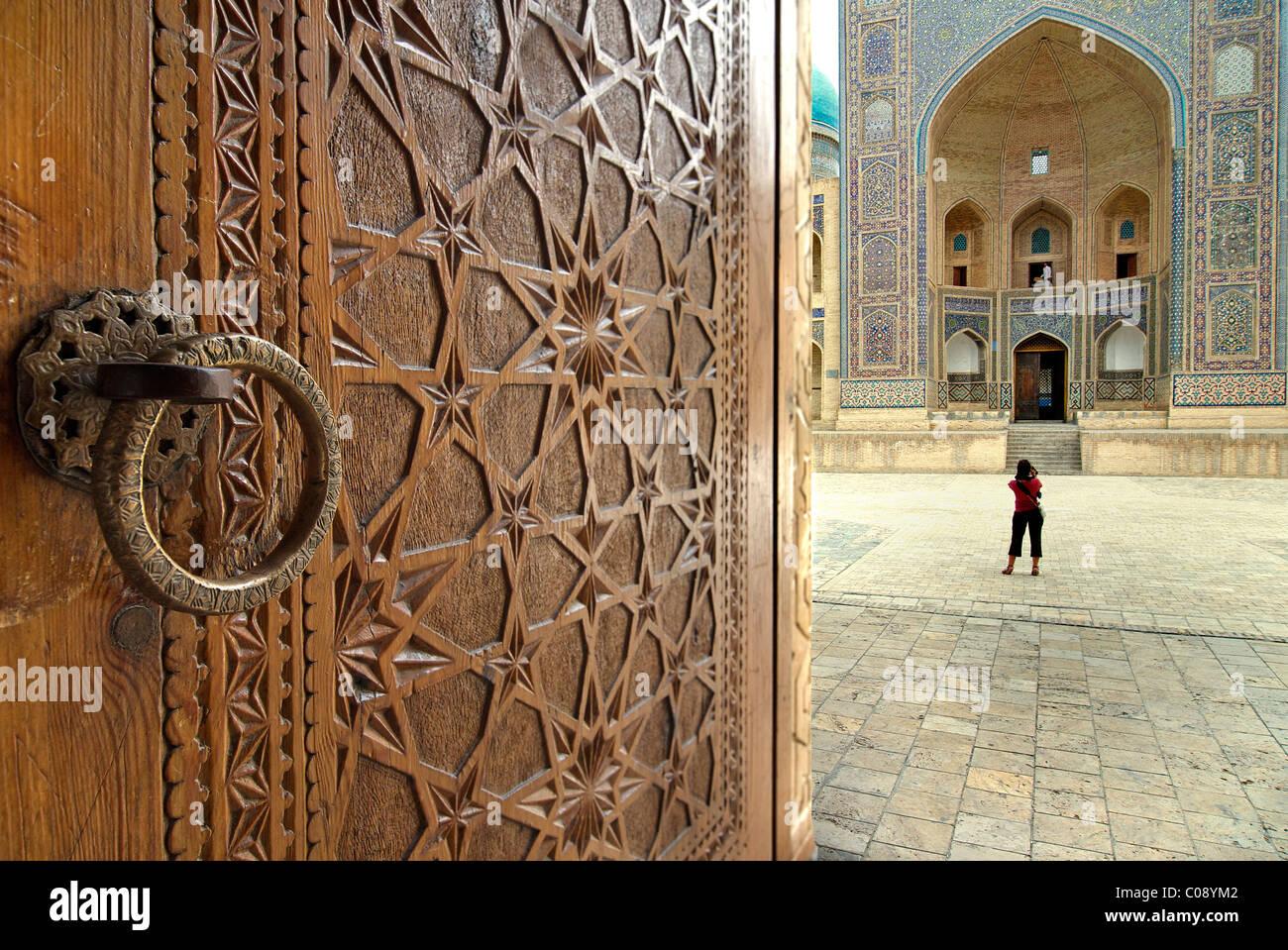 Die Mir-i-Arab Medrese gesehen über die kunstvollen geschnitzten Türen der Kalon-Moschee, Buchara, Usbekistan Stockbild