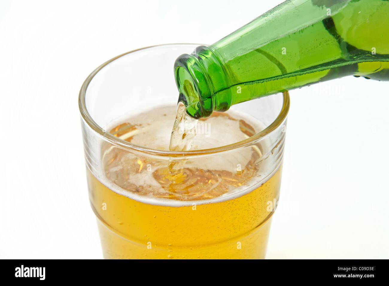Bier aus einer grünen Bierflasche in ein Glas gießen Stockbild