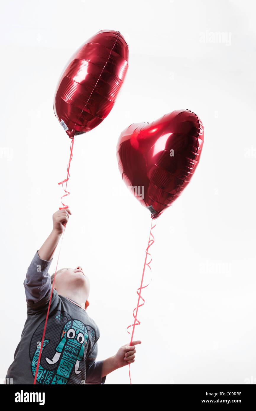 kleiner Junge hält einen herzförmigen Ballon Stockbild