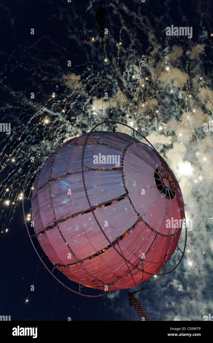 Ballon schwebt vor Feuerwerk, Globus, globale Rheingold, Open-Air-Theater von La Fura Dels Baus, Duisburg-Ruhrort Stockbild