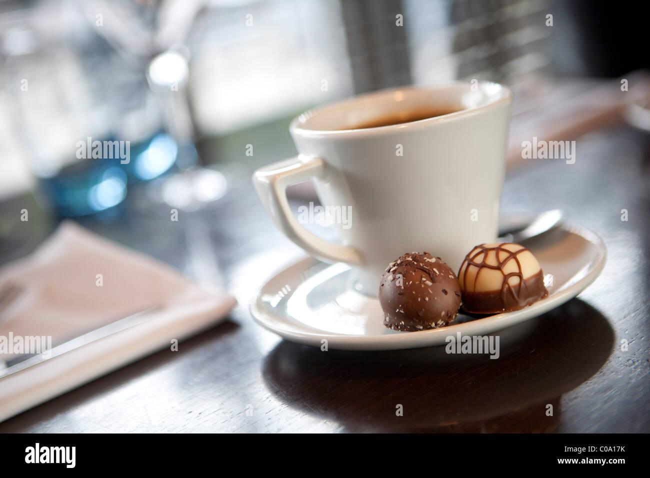 kaffeetasse mit 2 pralinen auf der untertasse auf einem tisch nach abendessen stockfoto bild. Black Bedroom Furniture Sets. Home Design Ideas