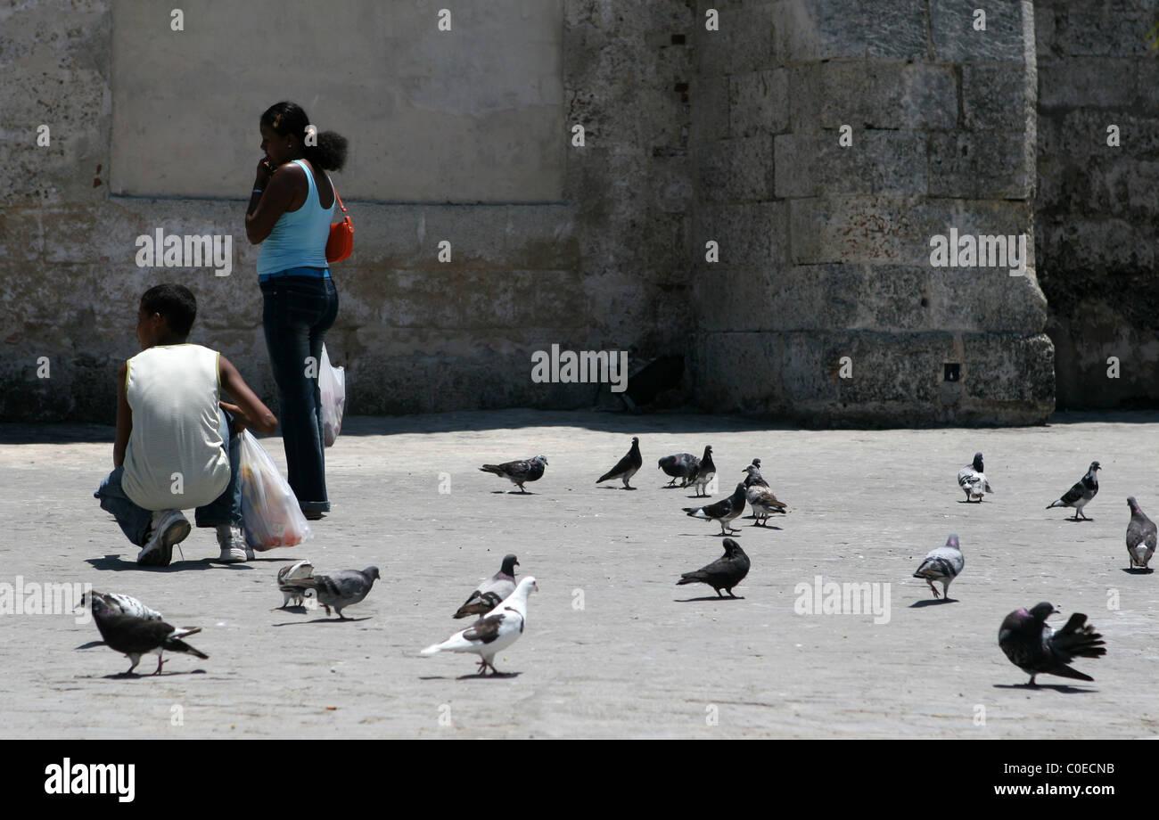 Kubaner, die Tauben füttern, außen Kloster und die Kirche San Francisco de Asis, am Plaza de San Francisco Stockbild