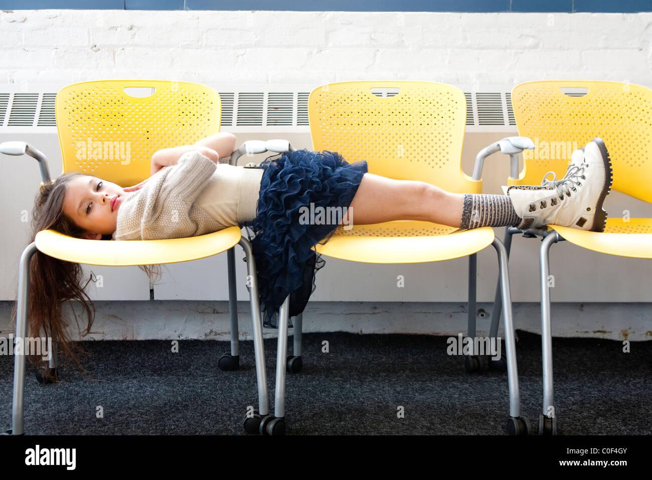 Mädchen, die Verlegung über gelbe Stühle Stockbild