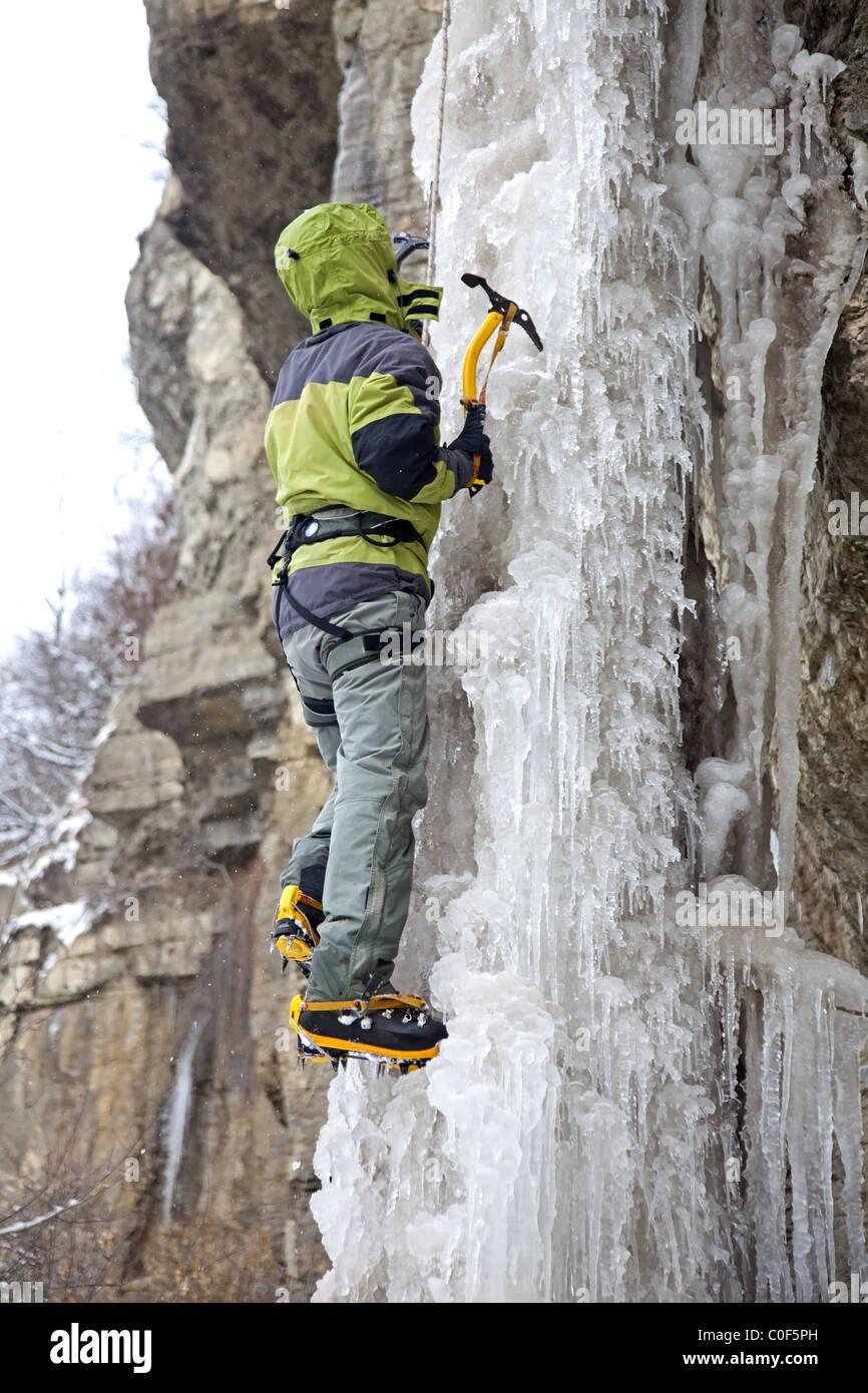 Mann mit Eispickel und Steigeisen Klettern am Eisfall Stockbild