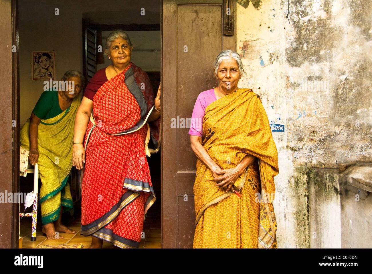 4e25bb819862b Drei alte indische Damen verkleidet mit bunten Saris vor einem alten Haus.  Stockbild