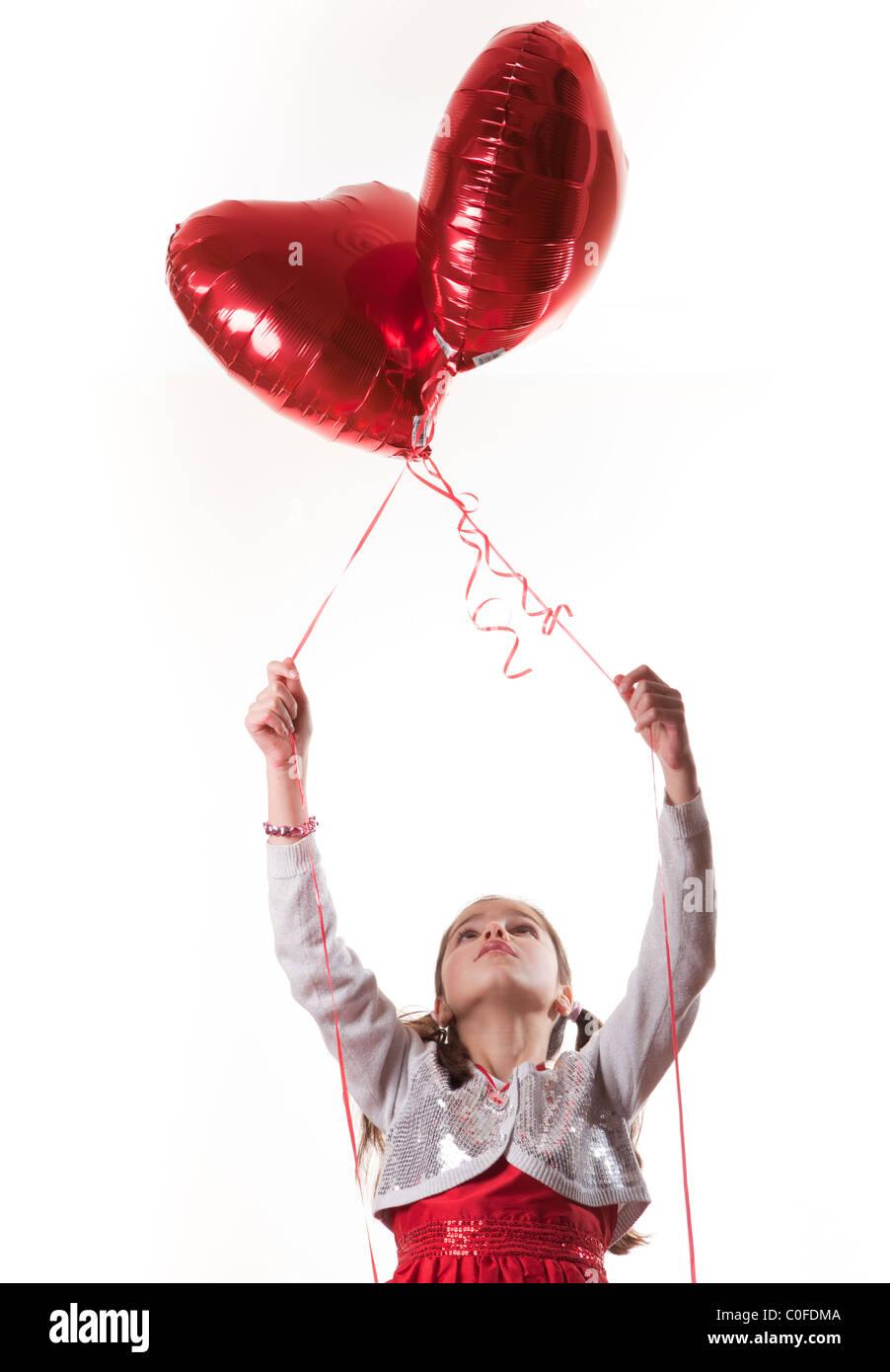 glückliches Mädchen hält Herz geformten Ballons Stockfoto