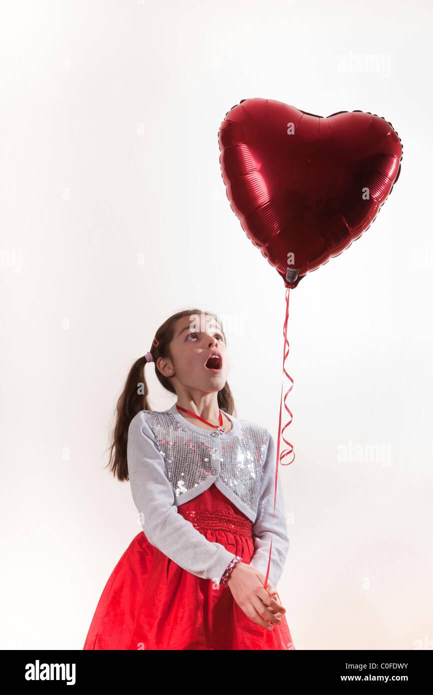 glückliches Mädchen hält einen Ballon in Herzform Stockfoto