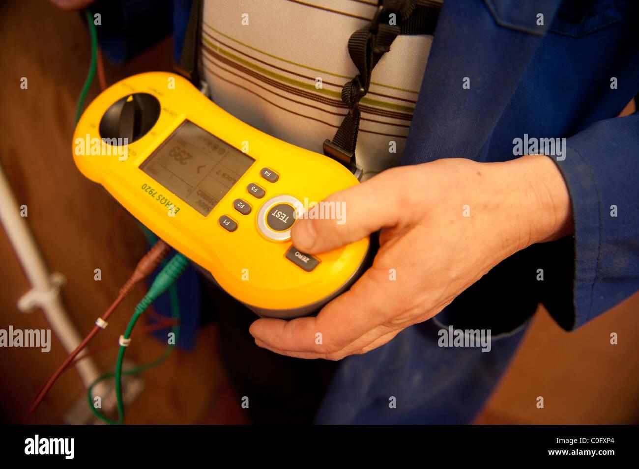 Ein Elektriker zu arbeiten PAT Tests ein elektrisches Gerät, UK Stockbild