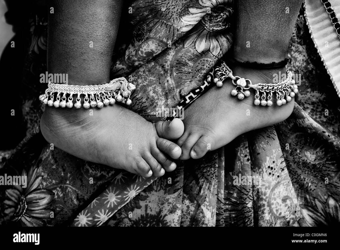 Indische Kinder barfuß gegen Mütter floral Sari. Monochrom Stockbild
