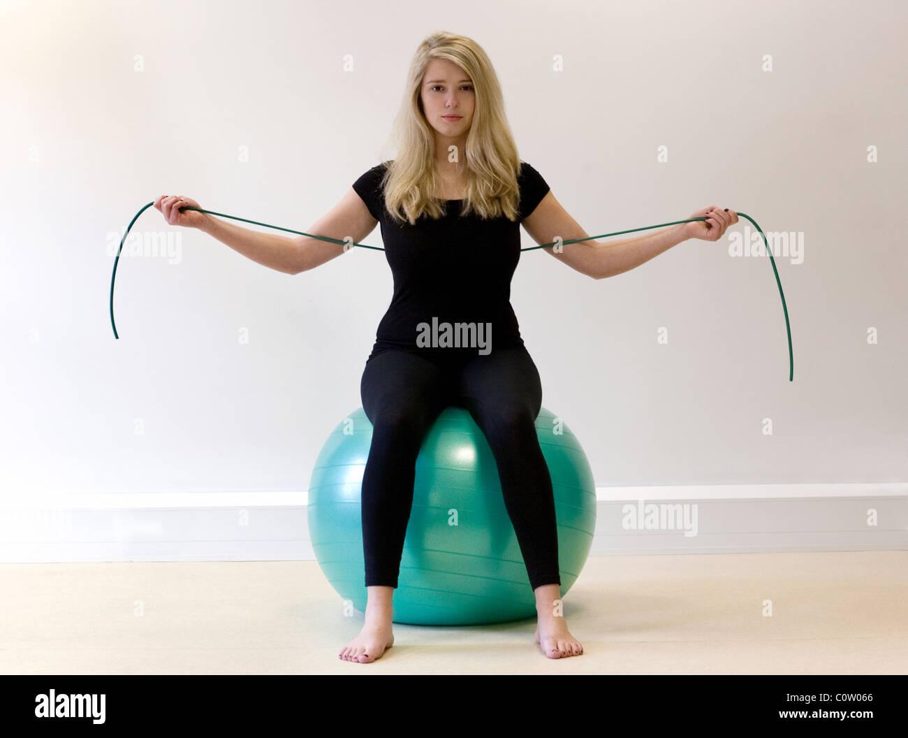 eine blonde teenager m dchen pilates bungen mit einem gymnastikball und eine elastische