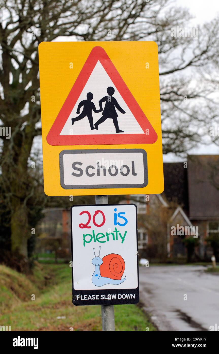 Schild am straßenrand schule und 20 km h langsamer bitte beschilderung auf einer zufahrtsstraße zu einem land schule hampshire uk