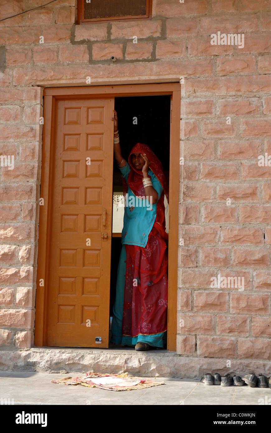 Der tur  Frau stand in der Tür ihres Rajasthani Dorfes nach Hause tragen ...