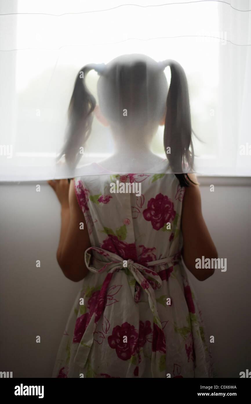 Mädchen schaut aus dem Fenster hinter der Gardine Stockbild