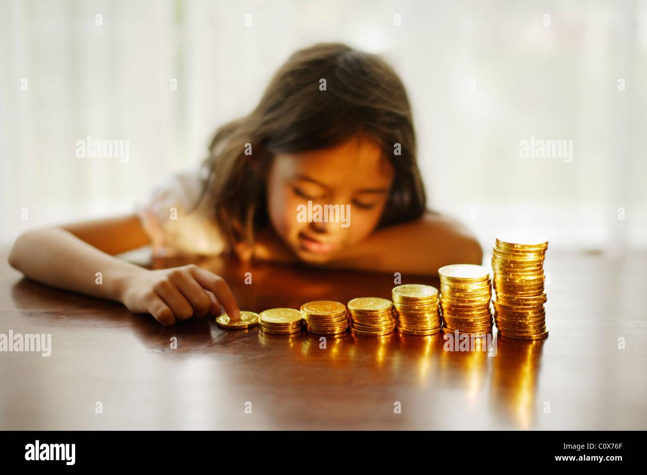Investieren in Gold. Mädchen mit gestapelten Schokoladen gold-Münzen. Stockbild