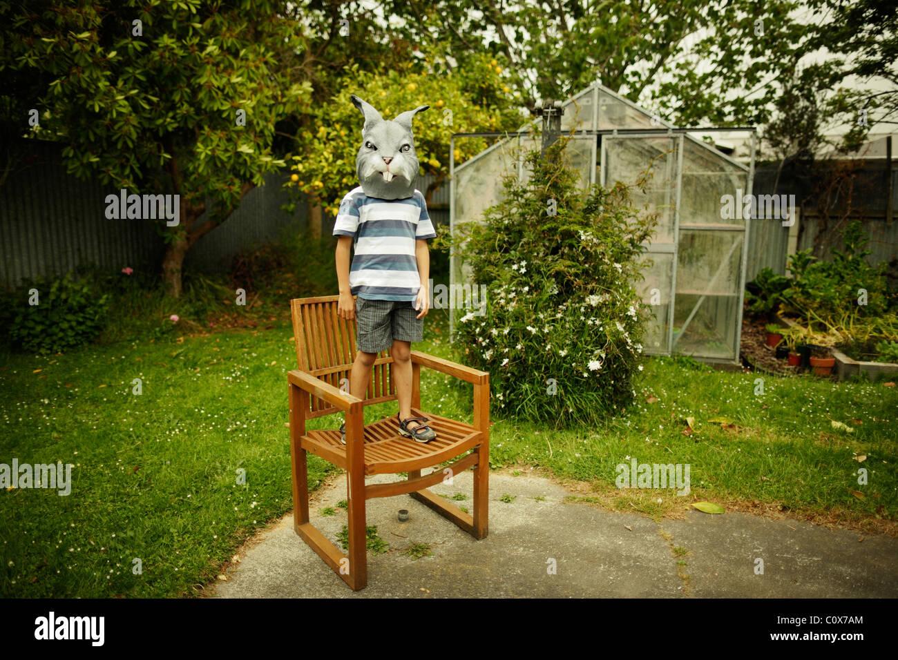 Junge mit Hasenmaske steht auf Sessel im Garten Stockbild