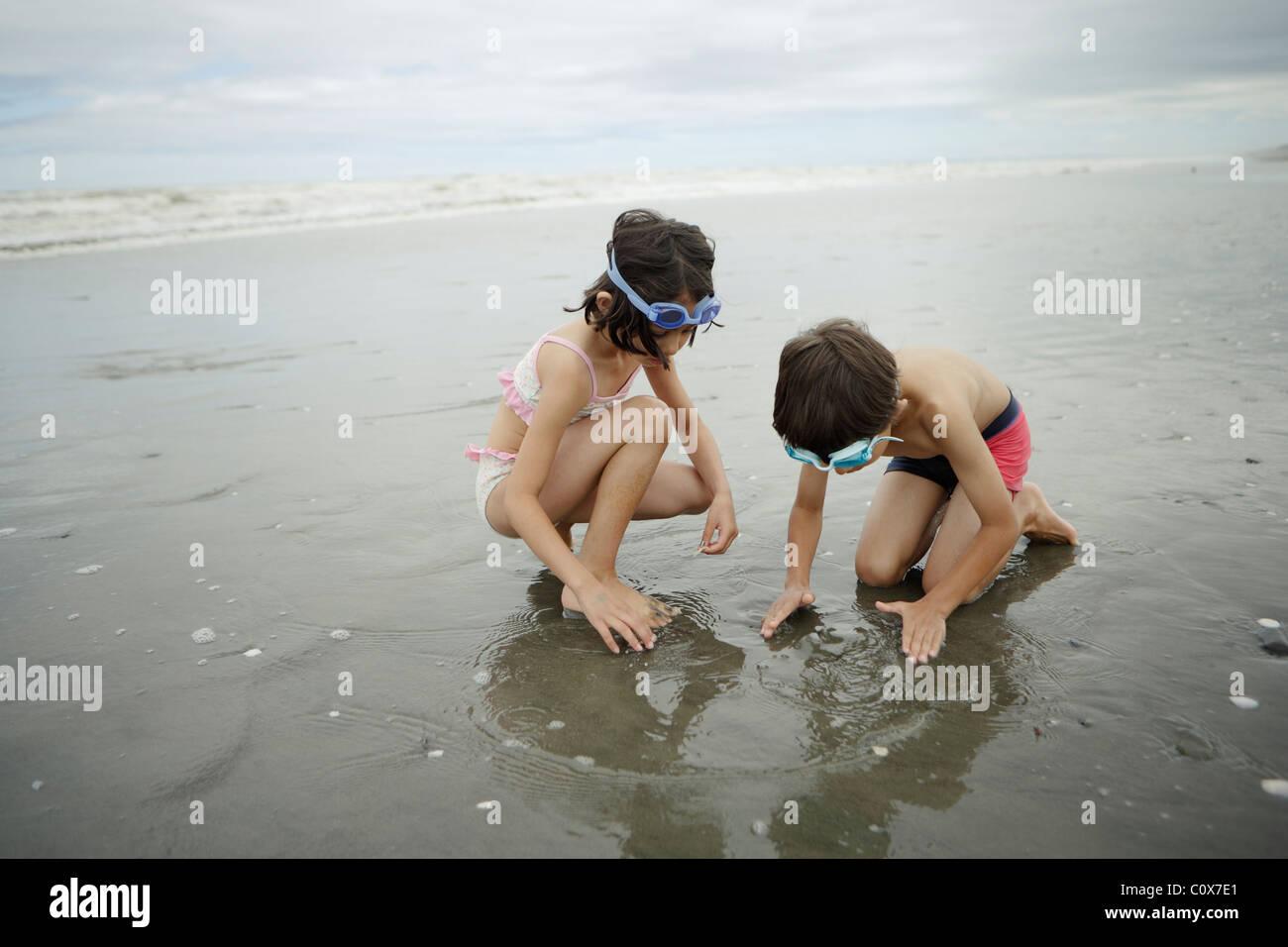 Spielen Sie Bruder und Schwester, Gemischte Rassen, im Meer. Manawatu, Neuseeland. Stockfoto