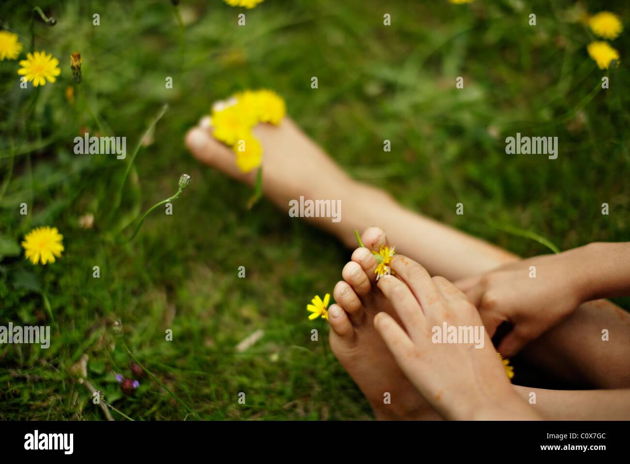 Mädchen setzt gelbe Blüten zwischen ihren Zehen. Stockbild
