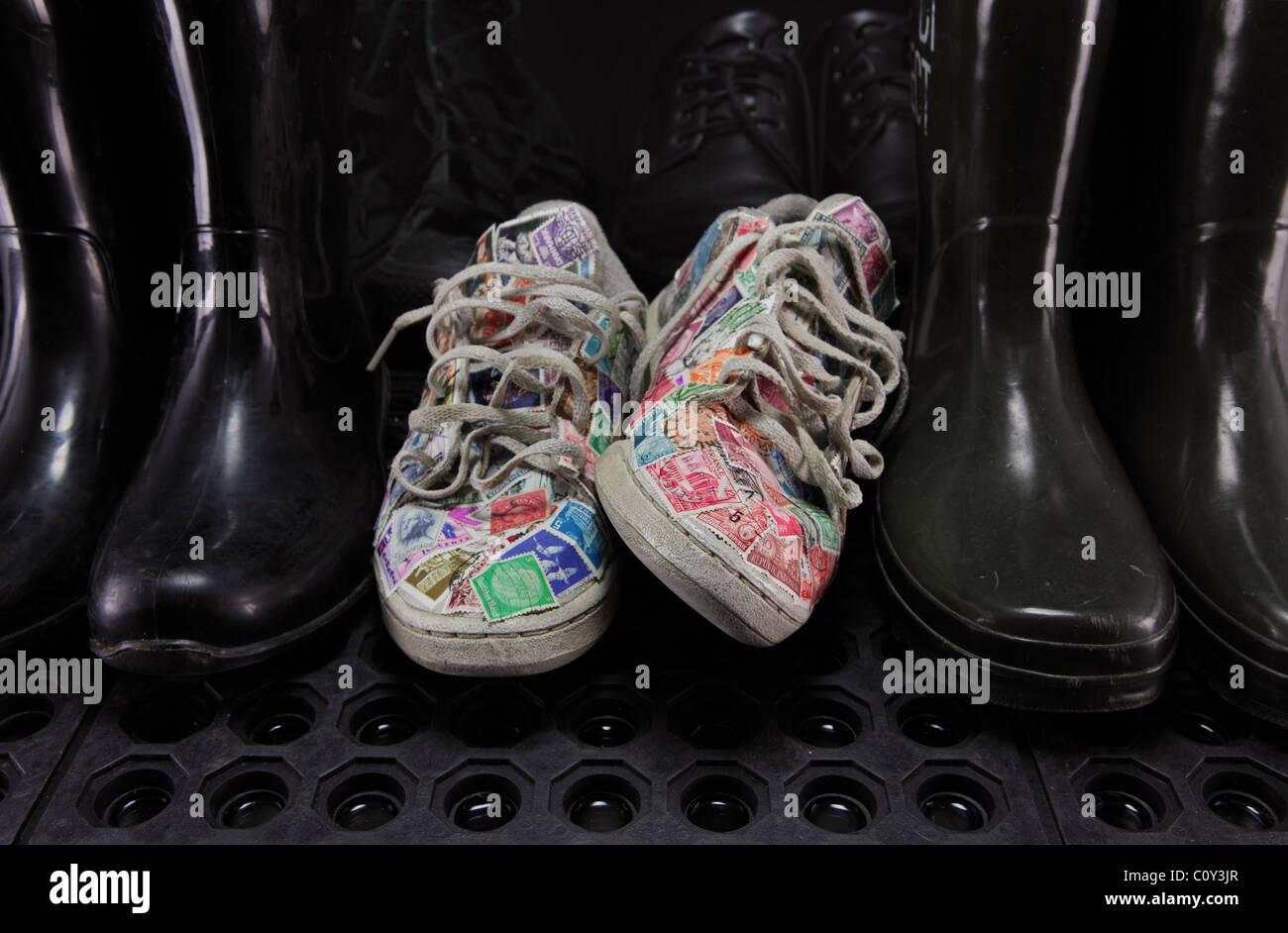 Laufschuhe mit Briefmarken, zwischen den dunklen und schwarzen Gummistiefeln und schwarzen Schuhen bedeckt. Stockbild