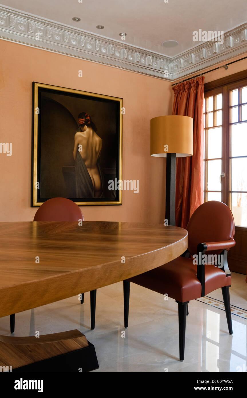 Oval geformte Esstisch mit Ledersesseln in Zimmer mit Marmorboden, vergoldet, gerahmte Gemälde und Friese Stockbild