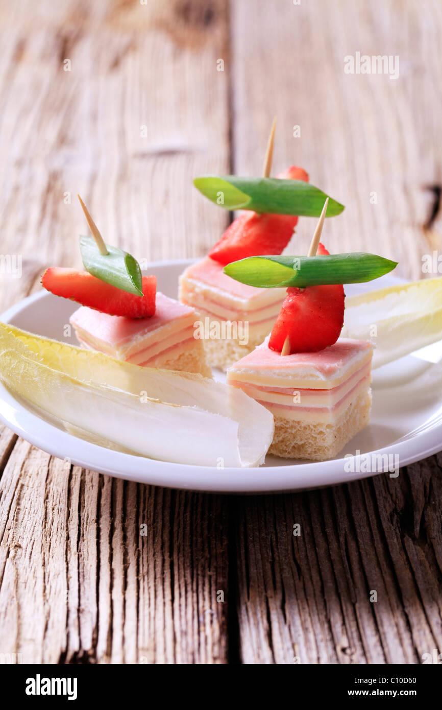 Schinken und Käse-Kanapees und frischer Endiviensalat Stockbild