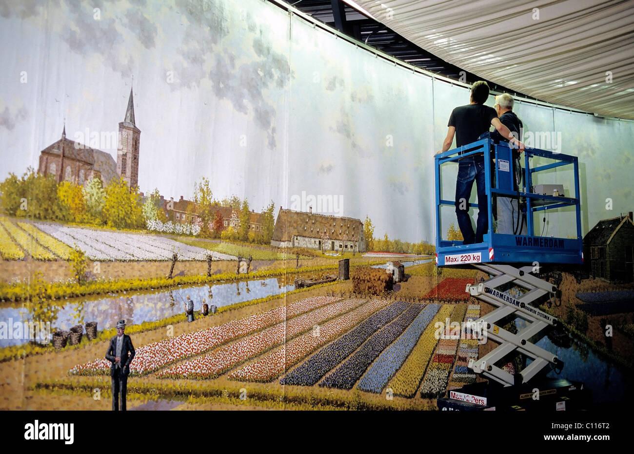 Maler auf einer Hebebühne vor einem Panoramabild, Tulipland von Leo van Den Ende, Vorhout, Süd-Holland, Stockbild