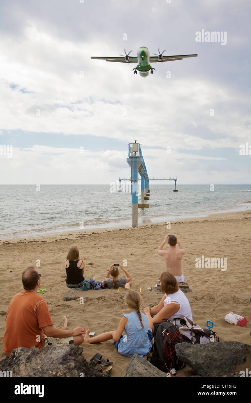 Eine Familie am Strand zu sitzen und ein Flugzeug zu sehen, wie es über Kopf fliegt kurz vor der Landung am Stockbild