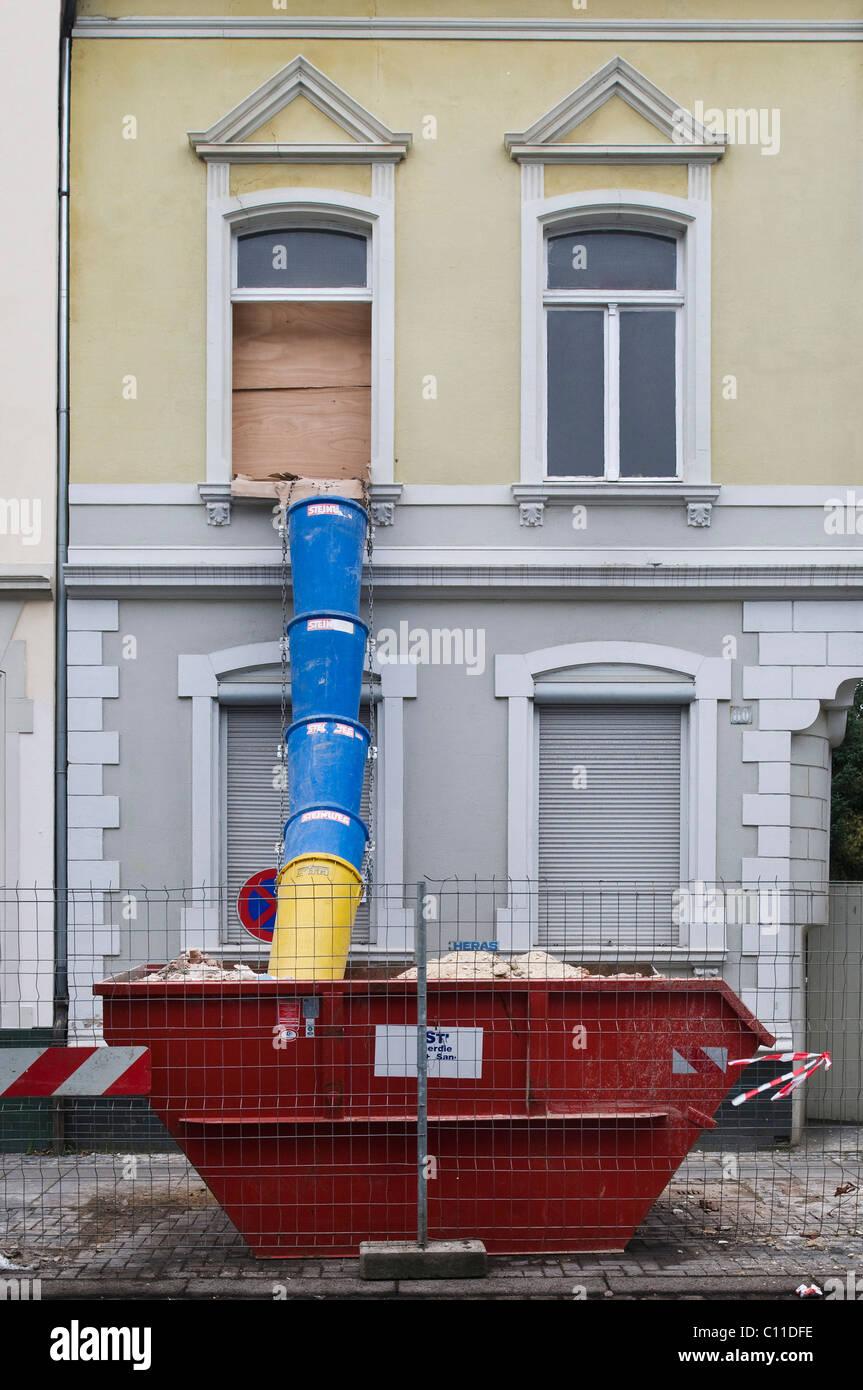 Überspringen Sie mit Dump Rohr vor einem Haus, das renoviert wird, Modernisierung, Kapitalanlage Stockbild