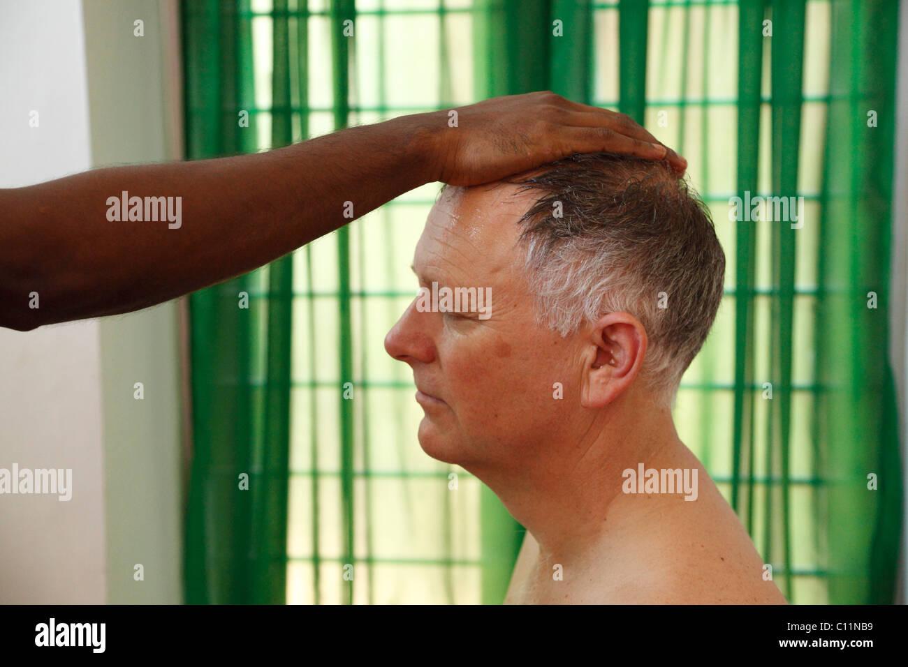 Verlegung einer Hand am Kopf des Mannes, Vorbereitung für Ayurveda-Behandlung, Bethsaida Hermitage in der Nähe Stockbild