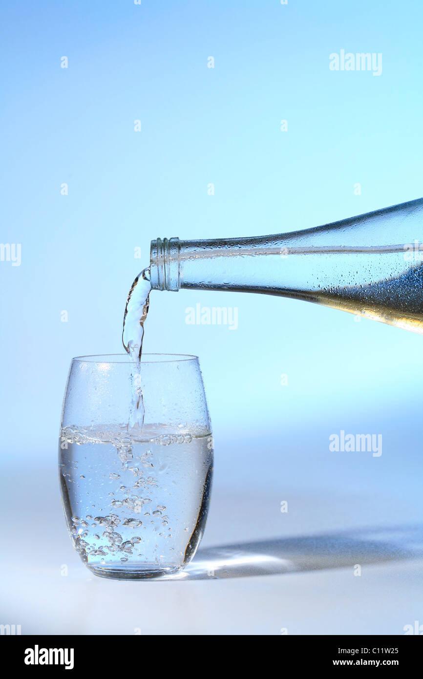 Mineralwasserflasche und ein Glas Wasser, Trinkwasser Stockbild