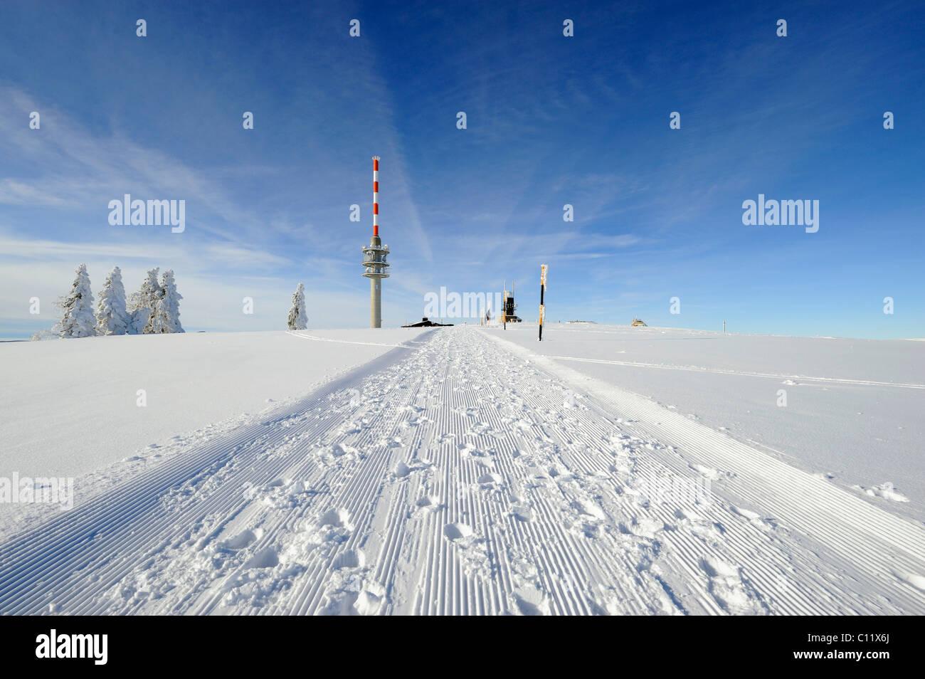 Gewalzten Schnee trail auf dem 1493m hohen Mt. Feldberg im Schwarzwald, am Horizont die neue Feldbergturm-Antenne Stockbild