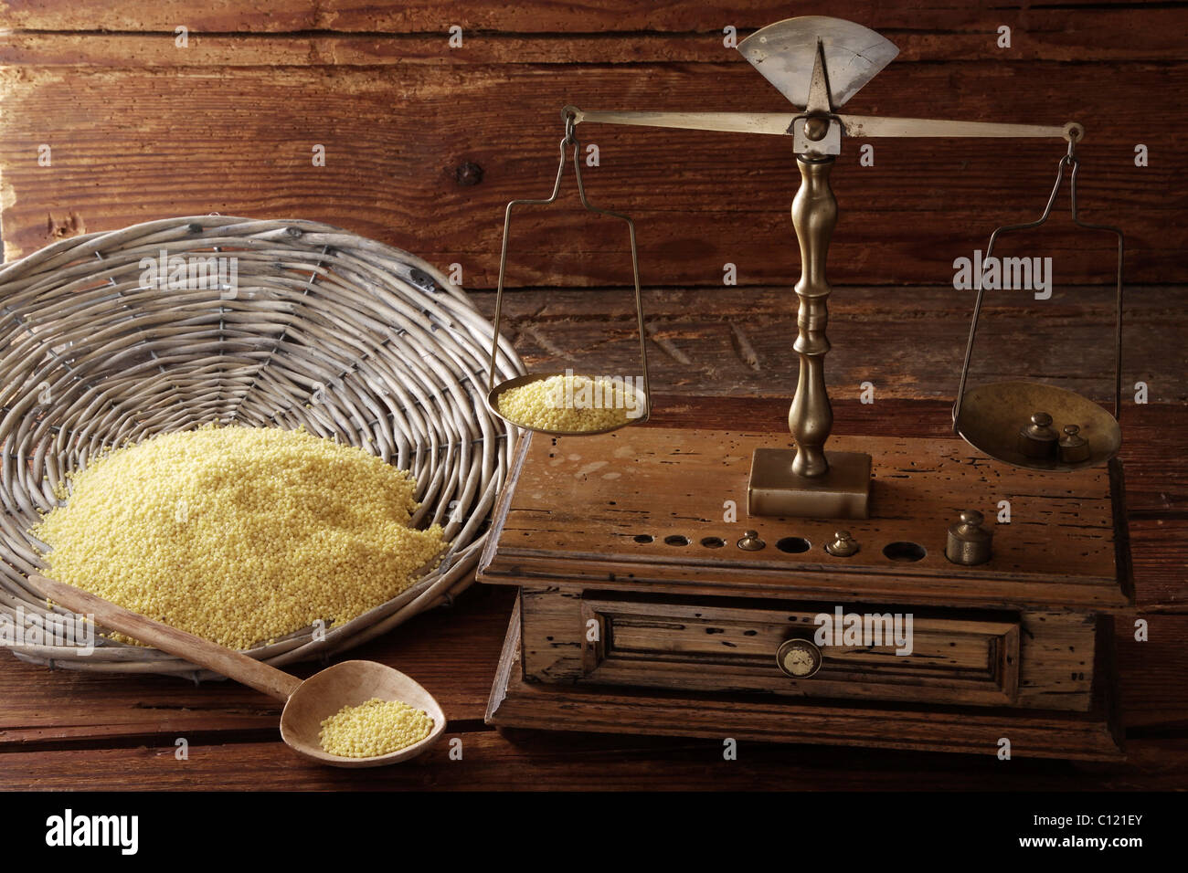 Antike Waage mit einem Gewicht von Getreide Hirse (Panicum Miliaceum) auf eine Holzoberfläche Stockbild