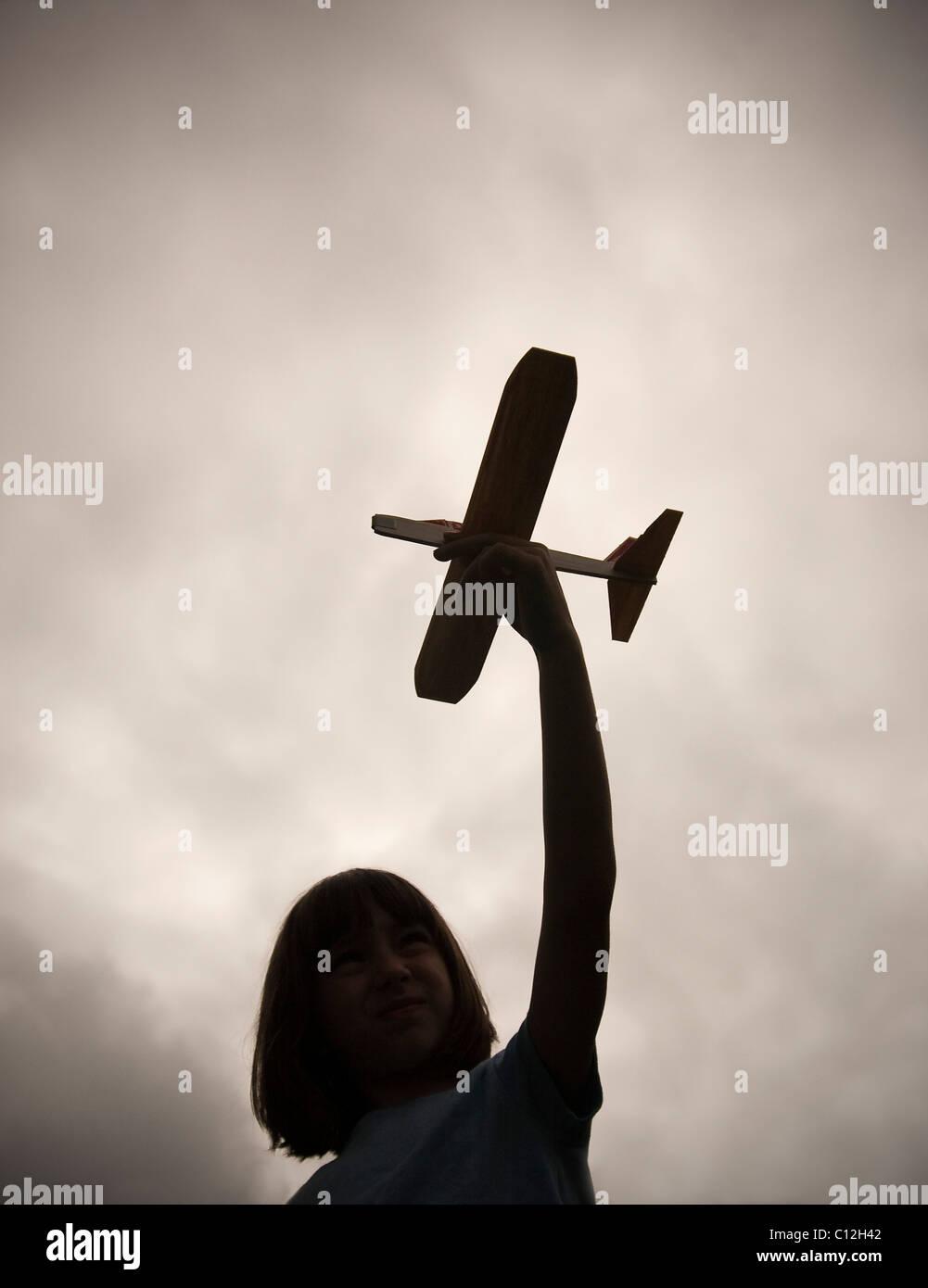 Ein Zehn Jahres altes Mädchen hält ein Spielflugzeug Balsa Holz, wie sie vor einem dunklen und trüben Himmel abhebt Stockfoto