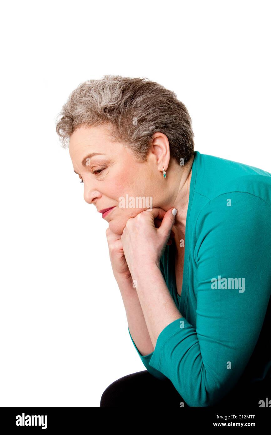 Schöne ältere Frau besorgt vornübergebeugt an ihren Händen an ihre zukünftigen oder vergangenen Leben isoliert. Stockfoto