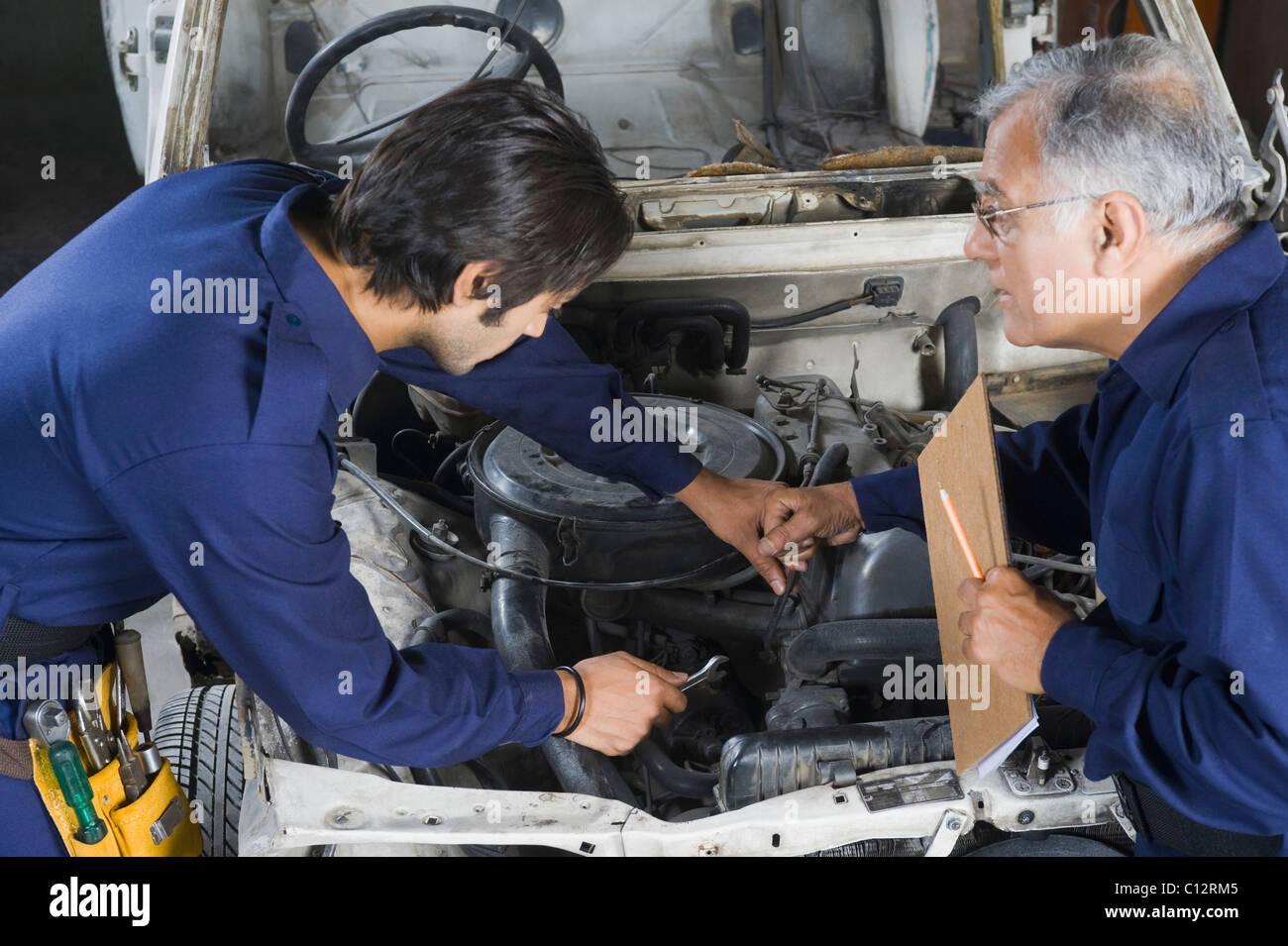 Kfz-Mechaniker mit Lehrling ein Auto in einer Garage reparieren ...