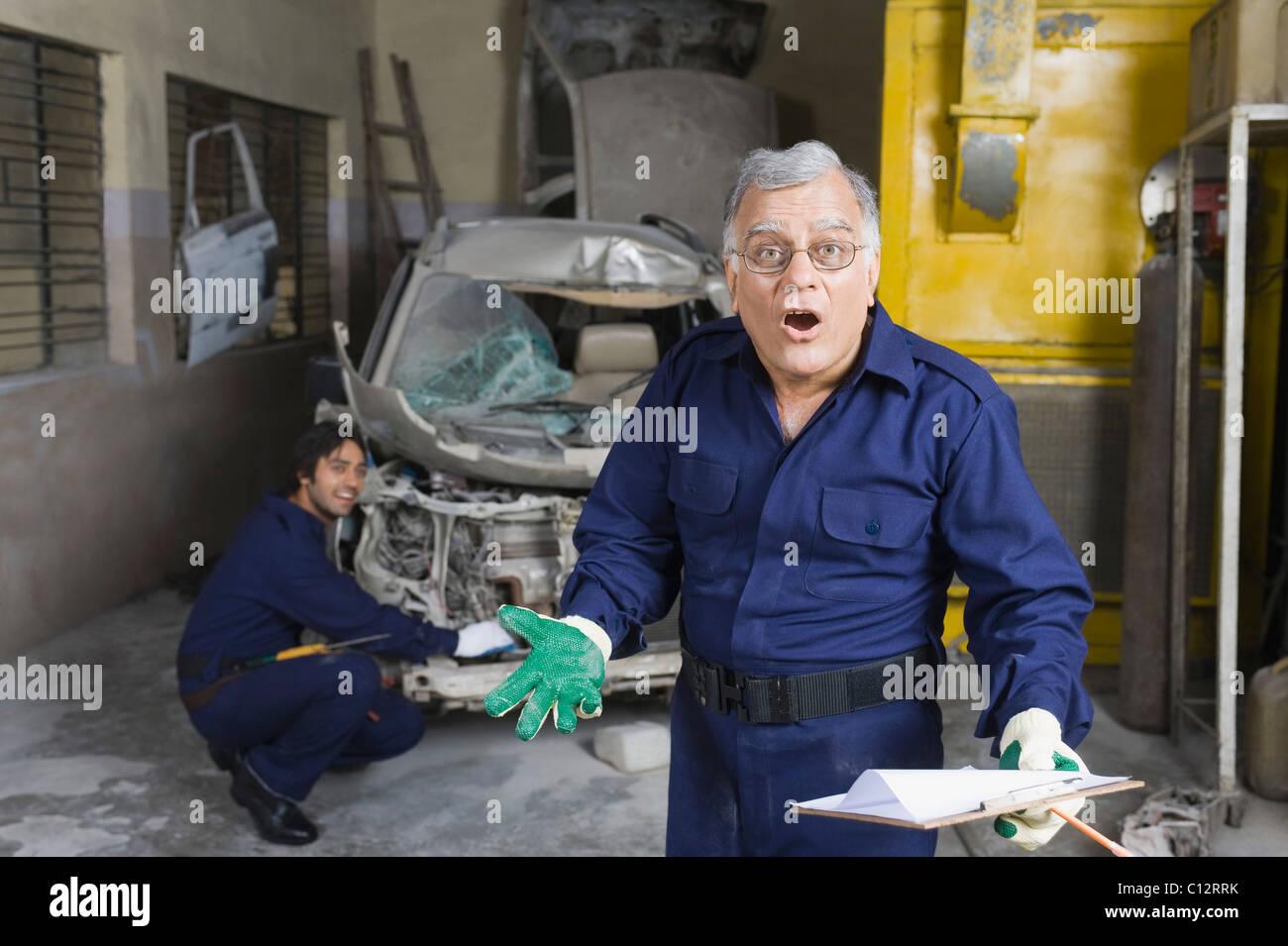 Porträt von Kfz-Mechaniker gestikulieren mit Lehrling reparieren ein ...