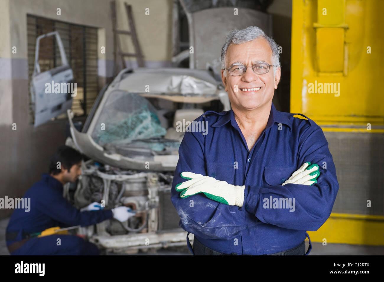 Porträt von lächelnd mit Lehrling ein Auto im Hintergrund Reparatur ...