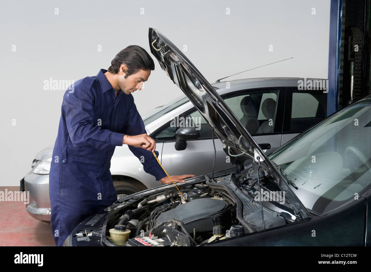 Kfz-Mechaniker Überprüfung Ölstand eines Autos in einer garage Stockbild