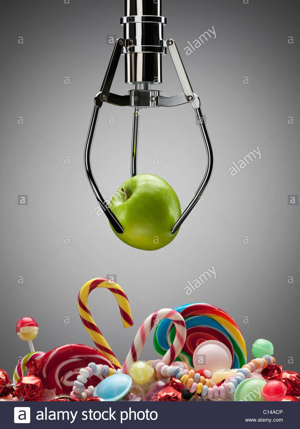 Haken Sie mit grünem Apfel über verschiedene süße Bonbons Stockbild