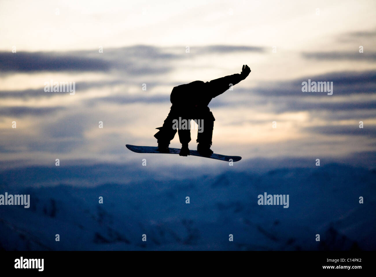 Eine männliche Snowboarder macht einen Backside 180 mute Grab während der Fahrt ein Snowpark in Wanaka, Stockbild