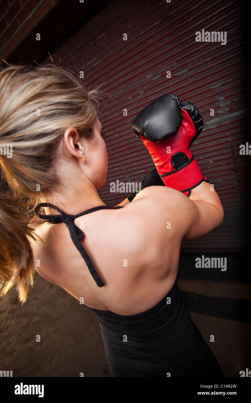 Ein junges Mädchen setzt auf ein Boxhandschuh vor dem Training für mixed Martial Arts außerhalb einer Stockbild
