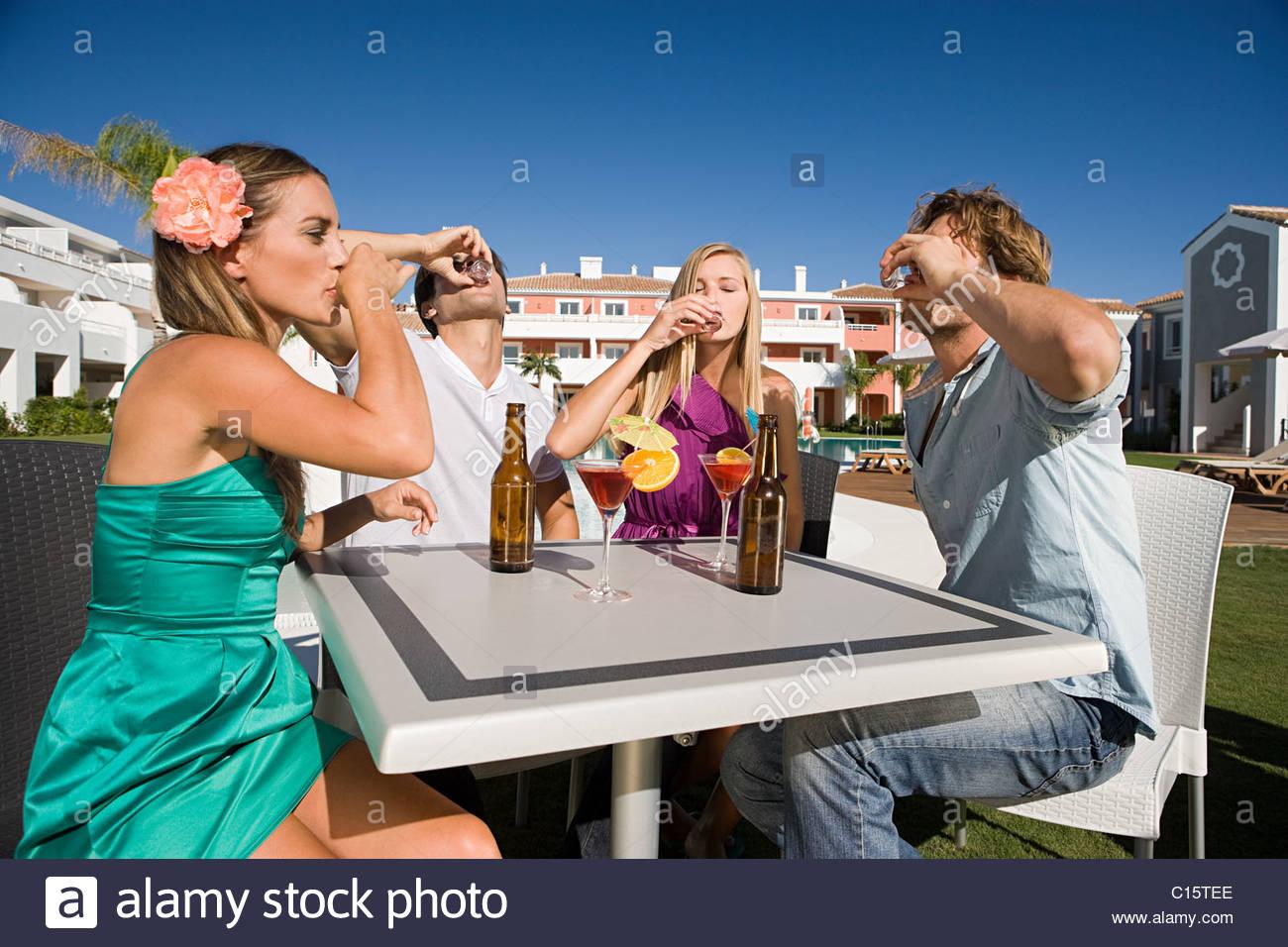 Vier Freunde trinken Aufnahmen im Urlaub Stockbild