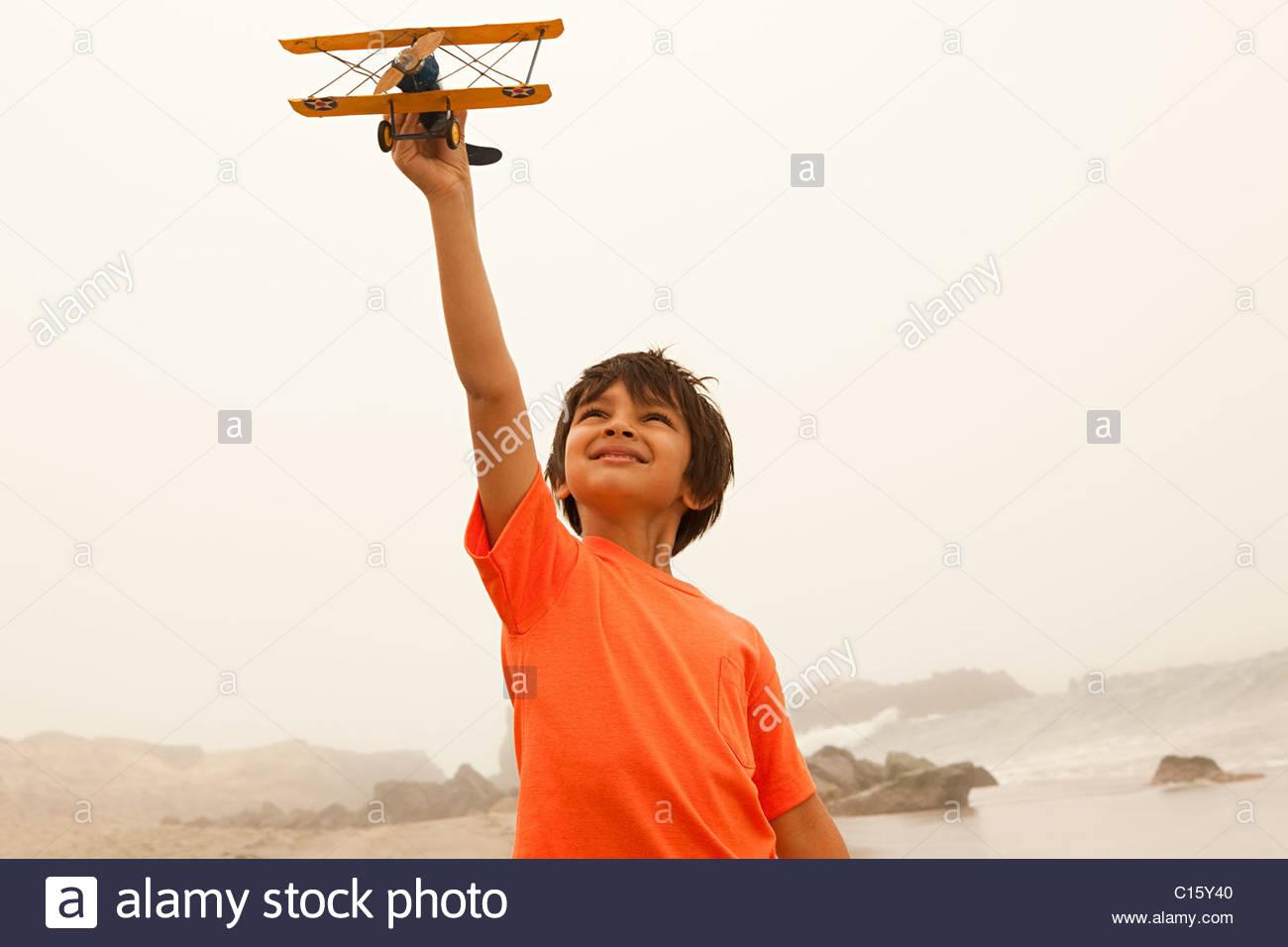 Jungen tragen orange t-Shirt spielen mit Spielzeug Flugzeug Stockbild