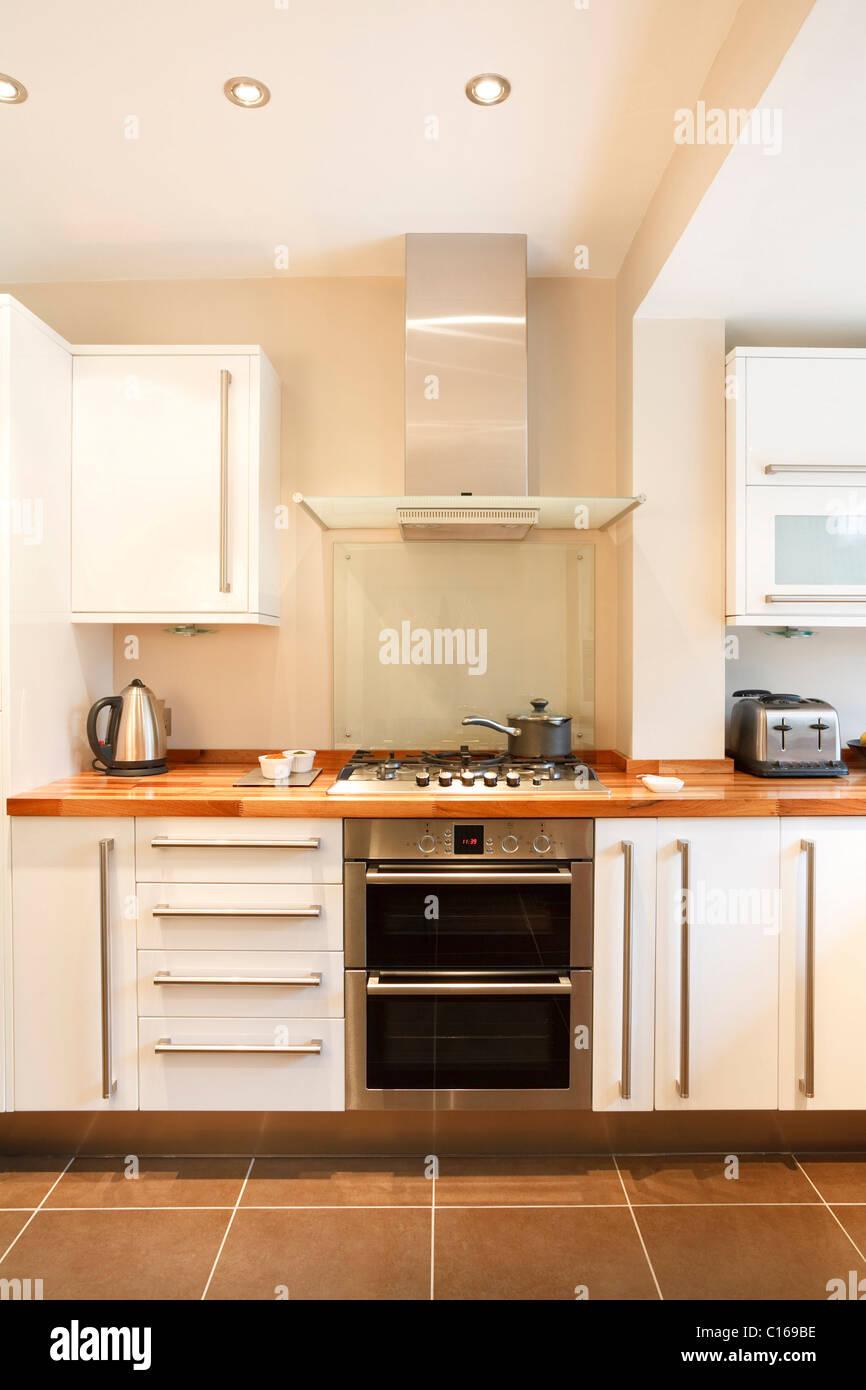 Moderne weiße Küche mit Holz Arbeitsplatten und Geräten aus rostfreiem Stahl Stockbild