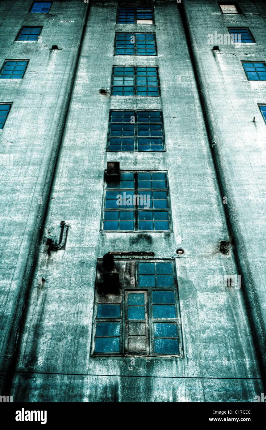 Unheimliche verlassene dunkles blaue Gebäude mit blauen Fenstern Stockbild