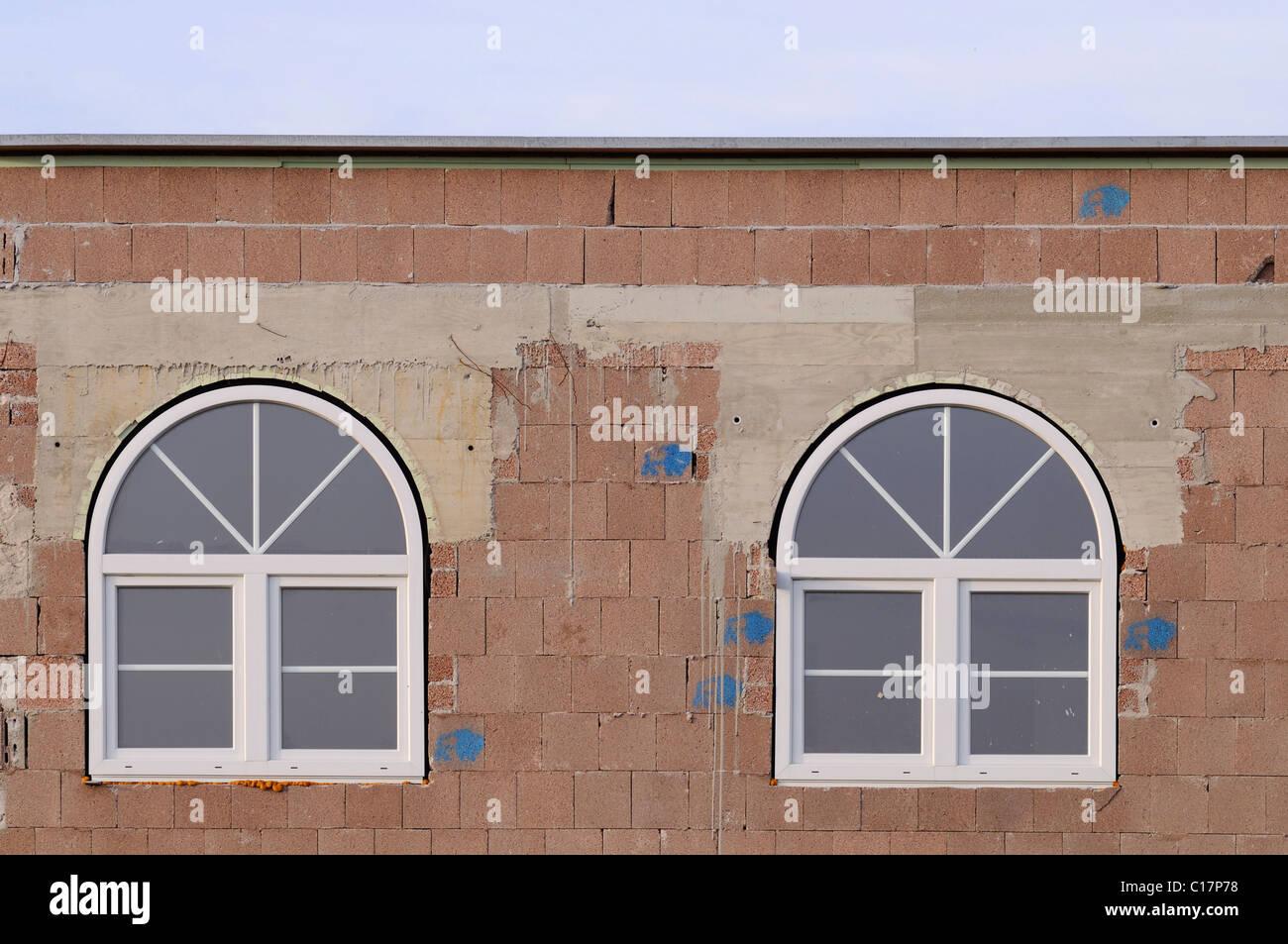 Rohes Mauerwerk mit neu erbaute Runde Bogenfenstern, isolierte Verglasung Stockbild
