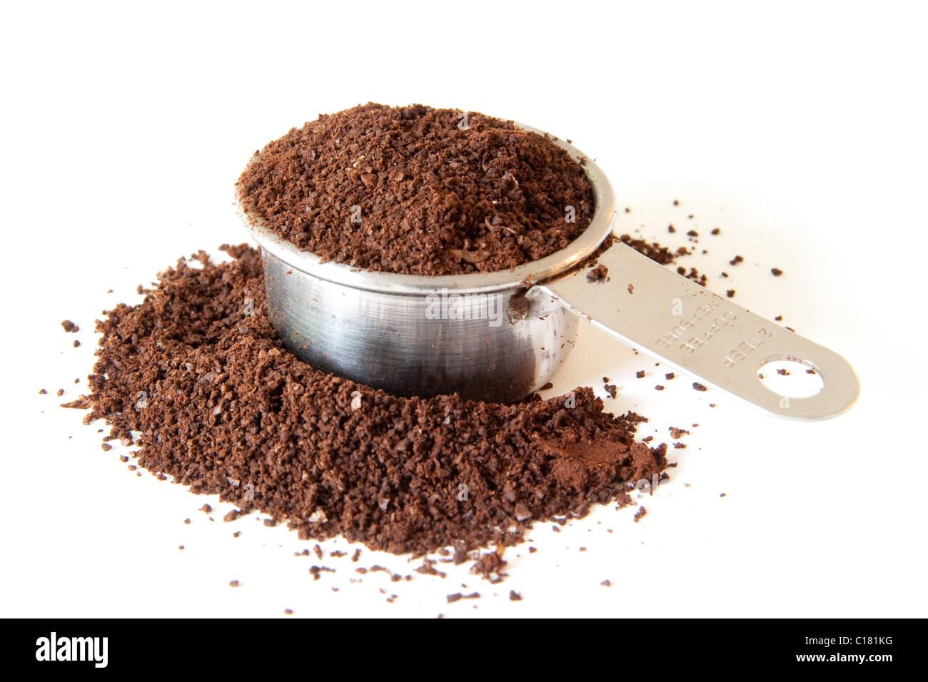 Gemahlener Kaffee verschütten aus einer vollen Kaffee Maßnahme. Schuss auf weißem Hintergrund. Schwerpunkt Stockbild