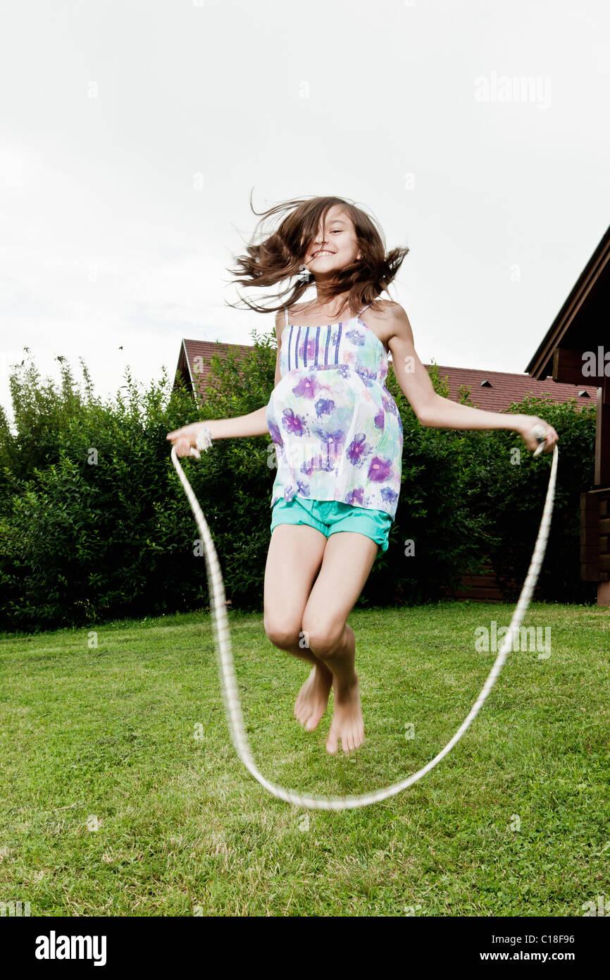 Mädchen im Garten überspringen Stockbild