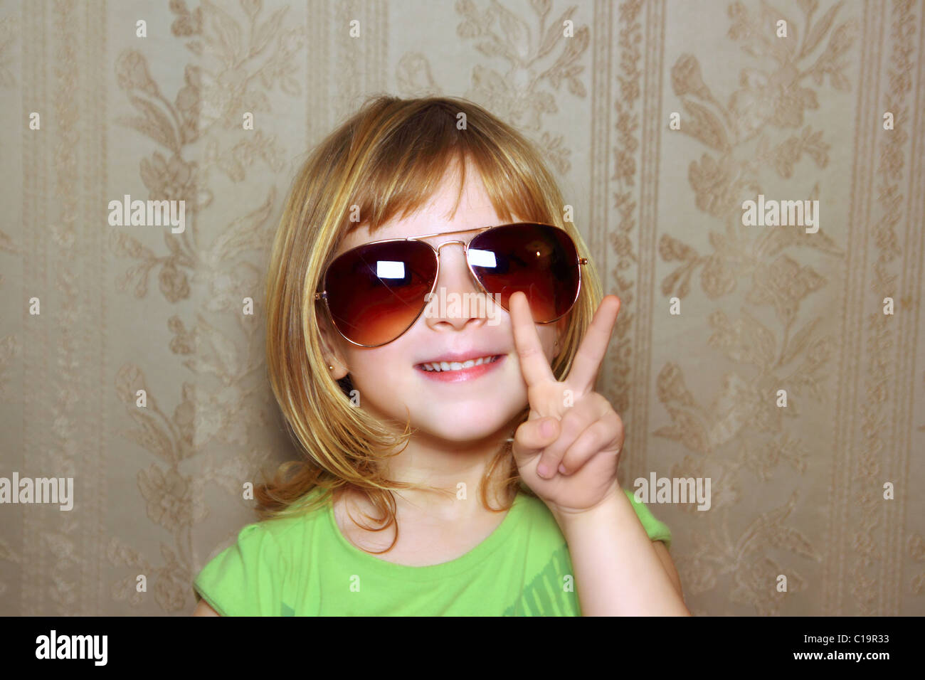 kleine Mädchen lustige Sonnenbrillen Retrotapeten Sieg Geste die Hand Stockbild